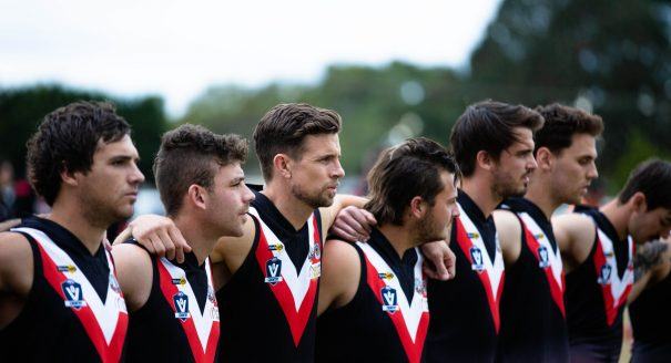 Devon Meadows players, including Brett Delidio, standing for a minutes silence. (Credit: Trent Moore)